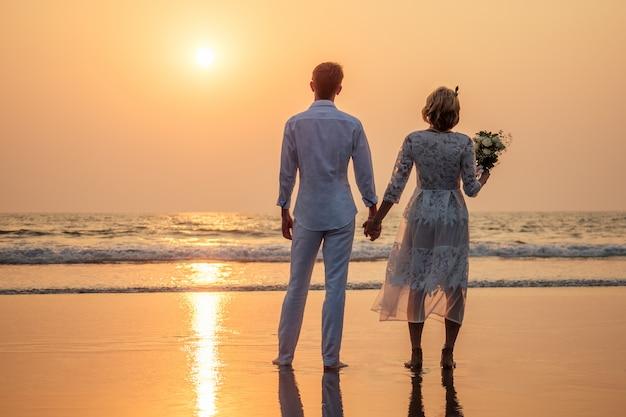 Noiva e noivo felizes na praia
