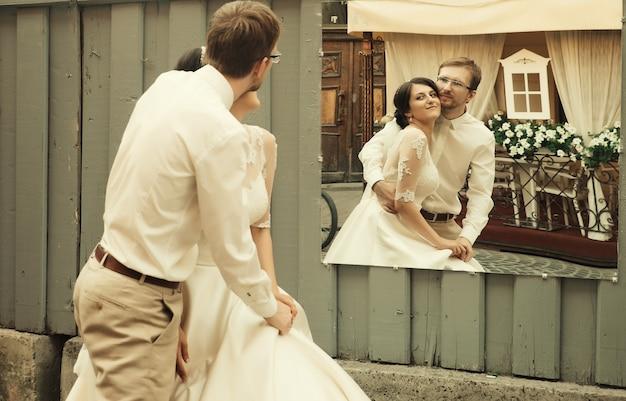 Noiva e noivo felizes românticos de luxo celebrando casamento no fundo da velha cidade ensolarada