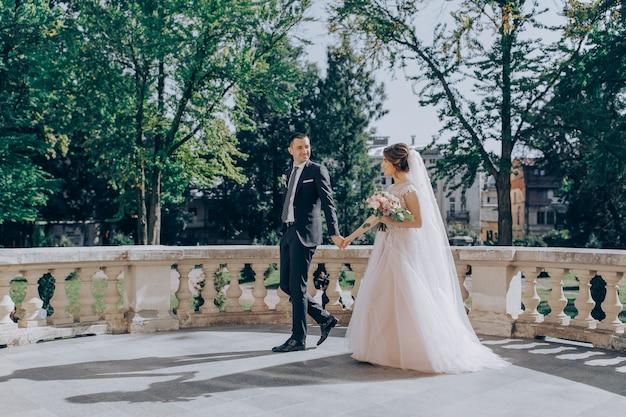 Noiva e noivo indo embora no parque de verão