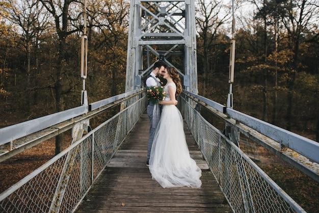 Noiva e noivo jovens felizes em uma ponte suspensa