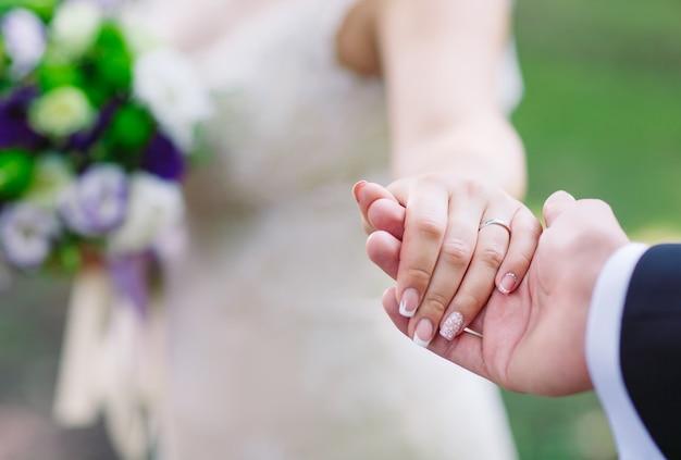 Noiva e noivo mãos, close-up.