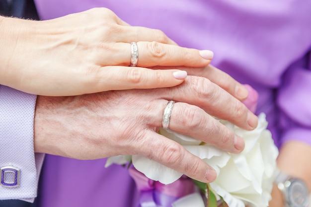 Noiva e noivo mãos com anéis de casamento contra e bouquet de noiva de flores