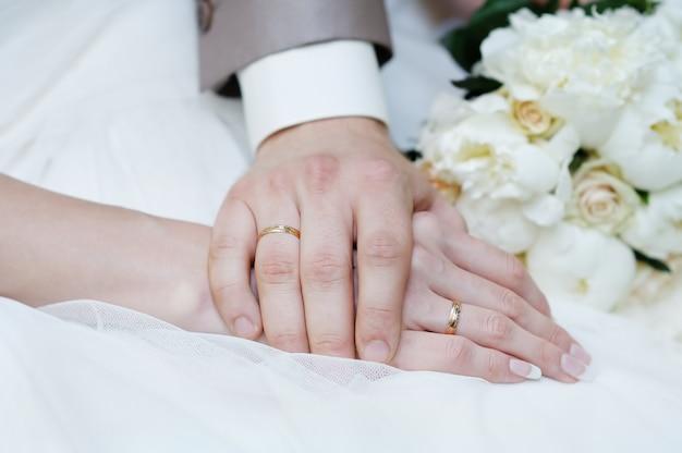 Noiva e noivo mãos com anéis de casamento