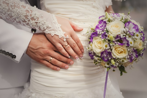 Noiva e noivo mãos com buquê de casamento e anéis