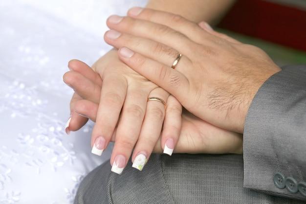 Noiva e noivo mostram as mãos usando anéis de casamento. amor e relações familiares