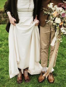 Noiva e noivo mostram seus sapatos no fundo de um campo, gramado verde