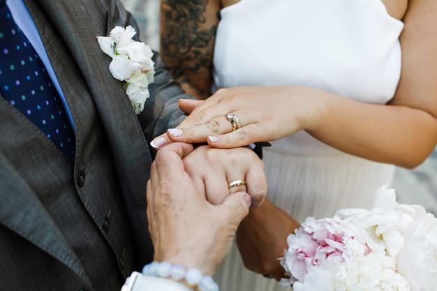Noiva e noivo mostram suas mãos com anéis de casamento
