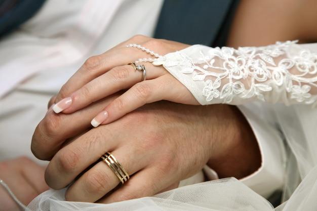 Noiva e noivo mostrando as mãos usando alianças