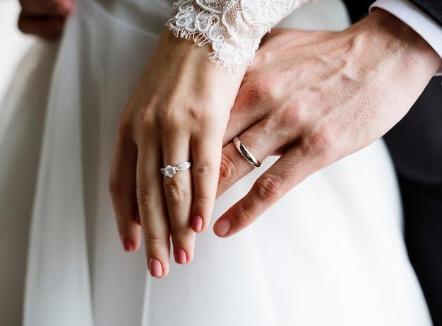 Noiva e noivo mostrando seus anéis de casamento de noivado nas mãos