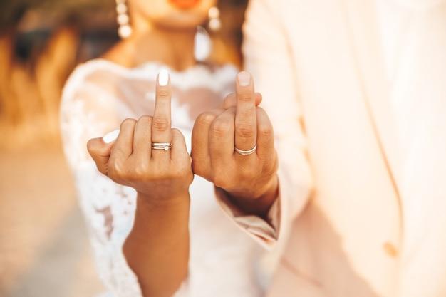 Noiva e noivo mostrando seus anéis