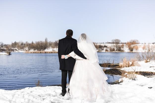 Noiva e noivo na neve olhando para o rio azul