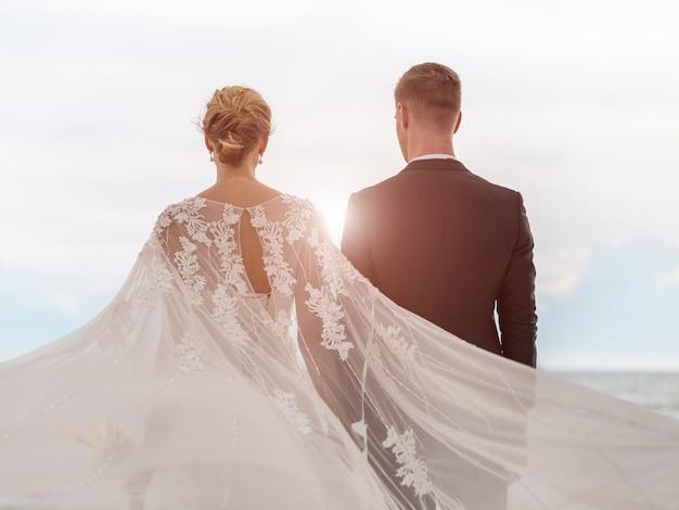 Noiva e noivo na praia com um momento romântico