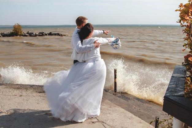 Noiva e noivo na praia olhando para o mar.