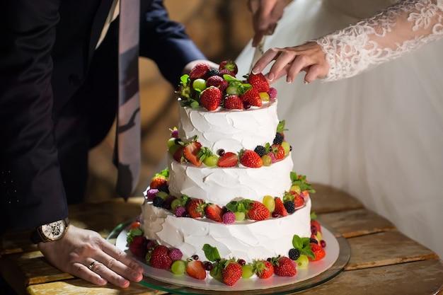 Noiva e noivo na recepção de casamento cortando o bolo de casamento
