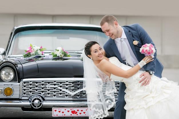 Noiva e noivo na rua perto do carro retrô