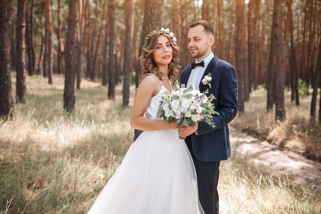 Noiva e noivo no casamento dia caminhando ao ar livre na natureza de verão