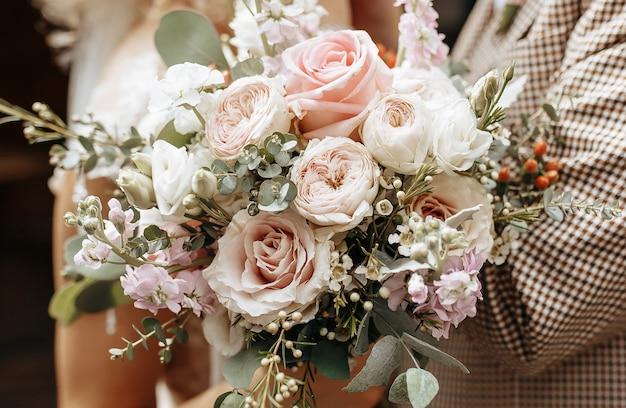 Noiva e noivo no dia do casamento abraçam e mostram amor com um buquê de flores rosas