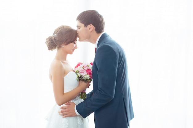 Noiva e noivo no quarto muito brilhante em casa
