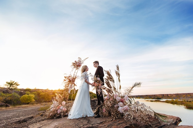 Noiva e noivo perto da decoração do casamento em uma cerimônia em um penhasco de rocha perto da água ao pôr do sol