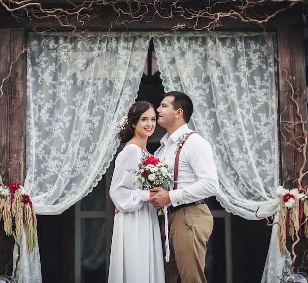 Noiva e noivo perto de arco.