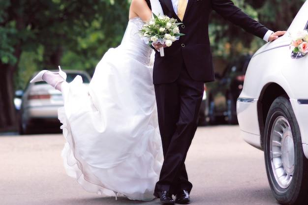 Noiva e noivo perto de limusine