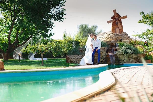 Noiva e noivo posando em um jardim