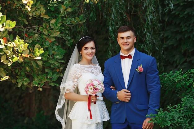Noiva e noivo posando em um parque