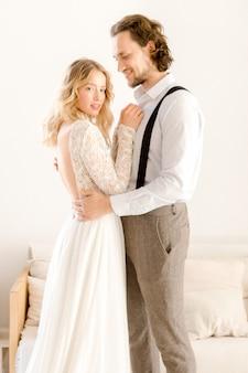 Noiva e noivo posando em um quarto brilhante