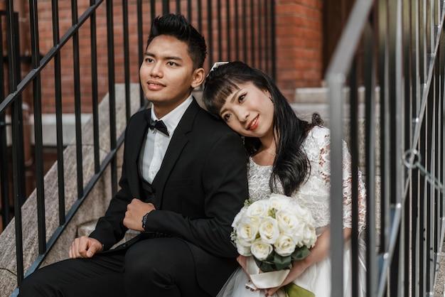 Noiva e noivo posando juntos em degraus
