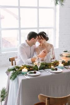 Noiva e noivo posando na mesa de banquete decorada no salão branco
