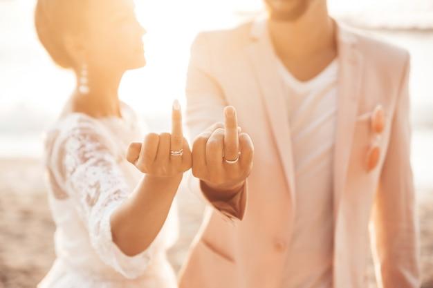 Noiva e noivo posando na praia ao pôr do sol