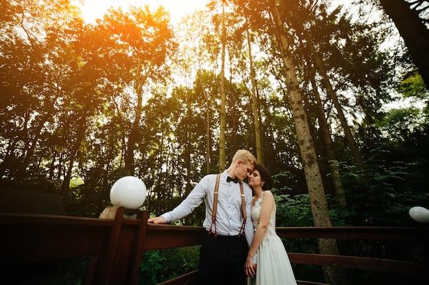 Noiva e noivo posando na varanda em algum lugar na natureza