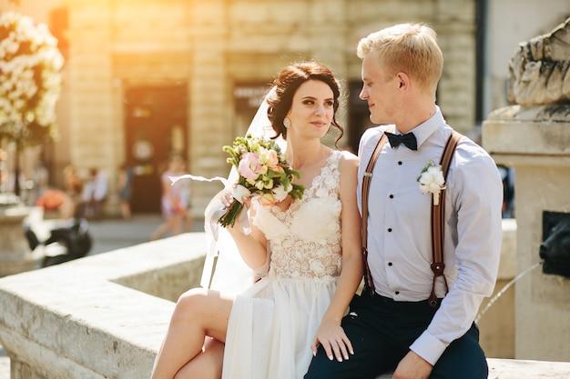 Noiva e noivo posando na velha fonte