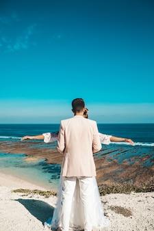 Noiva e noivo posando no penhasco atrás do céu azul e mar