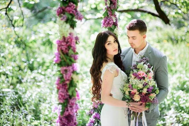 Noiva e noivo posta atrás de um grande círculo de lilás no jardim