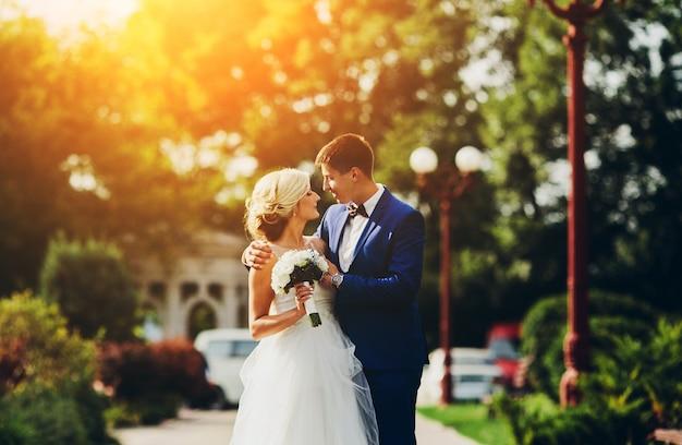 Noiva e noivo que andam pela rua