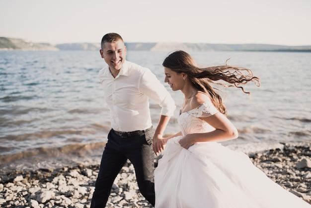Noiva e noivo rindo correm juntos