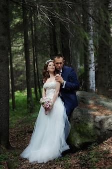 Noiva e noivo se abraçam e se beijam na floresta escura ao sol. casamento na natureza, retrato de um casal apaixonado no parque