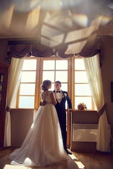 Noiva e noivo se abraçando e se beijando