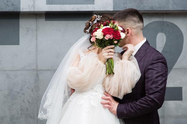 Noiva e noivo se beijam por um buquê