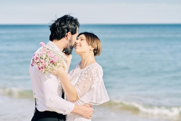 Noiva e noivo se beijando na praia comemorando o casamento