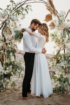 Noiva e noivo se casando na praia