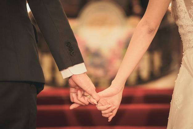 Noiva e noivo segurando a mão esperando a cerimônia de casamento