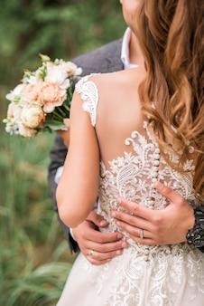 Noiva e noivo segurando buquê de casamento