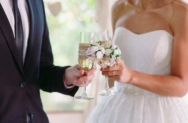 Noiva e noivo segurando copos de champanhe de casamento