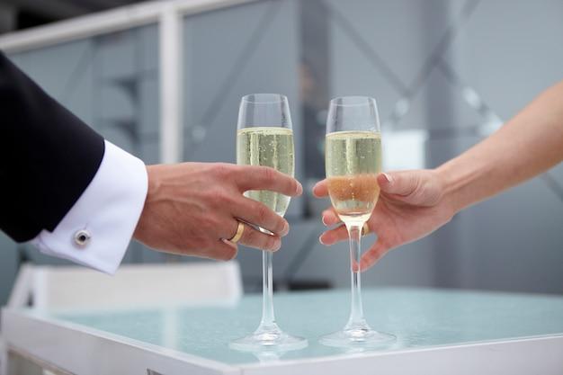Noiva e noivo segurando copos de champanhe