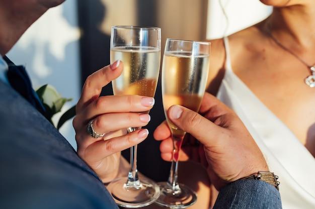 Noiva e noivo segurando nas mãos taças com vinho