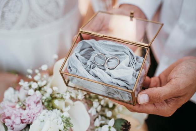 Noiva e noivo segurando seus anéis
