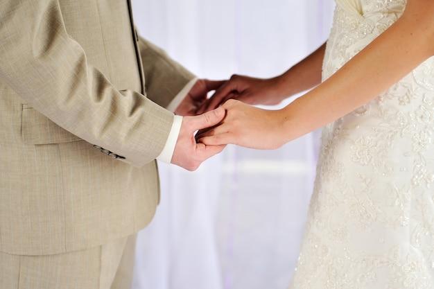 Noiva e noivo segurando suas mãos