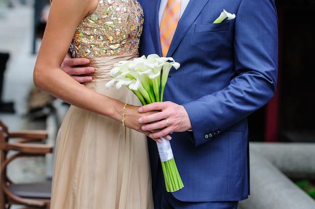 Noiva e noivo segurando um buquê de callas.